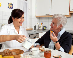 elderly having breakfast accompanied by caregiver